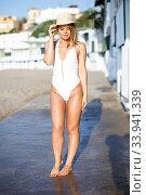 Купить «Sexy girl in swimsuit and hat posing near buildings at sea shore», фото № 33941339, снято 10 июля 2018 г. (c) Яков Филимонов / Фотобанк Лори