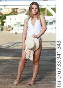 Купить «Attractive girl in swimsuit with hat standing near hotel at ocean shore», фото № 33941343, снято 10 июля 2018 г. (c) Яков Филимонов / Фотобанк Лори