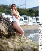 Купить «Young attractive girl in swimsuit and hat posing at sea shore», фото № 33941347, снято 10 июля 2018 г. (c) Яков Филимонов / Фотобанк Лори