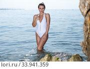 Купить «Portrait of young female in swimsuit posing and taking sunbath», фото № 33941359, снято 10 июля 2018 г. (c) Яков Филимонов / Фотобанк Лори