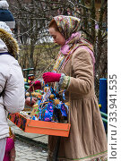Moscow, Russia, February 2020. A girl in an old national costume sells Souvenirs for Maslenitsa. Редакционное фото, фотограф Artem Sobov / Фотобанк Лори