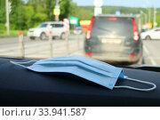 Купить «Медицинская маска на передней панели автомобиля. Масочный режим. Пандемия коронавируса COVID-19 в России, 2020 год», эксклюзивное фото № 33941587, снято 7 июня 2020 г. (c) Щеголева Ольга / Фотобанк Лори