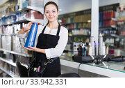 Positive girl hairstylist in apron showing shampoo in studio. Стоковое фото, фотограф Яков Филимонов / Фотобанк Лори