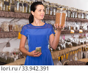 Купить «adult female choosing natural dried herbs sold by weight in eco shop», фото № 33942391, снято 13 июня 2017 г. (c) Яков Филимонов / Фотобанк Лори