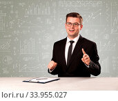 Купить «Young handsome businessman sitting at a desk with white graphs and calculations behind him», фото № 33955027, снято 7 августа 2020 г. (c) easy Fotostock / Фотобанк Лори