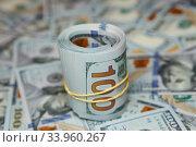 Купить «dollar roll on background of many dollars», фото № 33960267, снято 6 апреля 2016 г. (c) Nataliia Zhekova / Фотобанк Лори