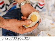 caring young father dresses shoes for his newborn son. Стоковое фото, фотограф Nataliia Zhekova / Фотобанк Лори