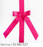 Pink ribbon with bow on white background. Стоковое фото, фотограф Nataliia Zhekova / Фотобанк Лори