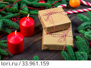 Купить «Two gifts wrapped in craft paper next to red burning candles on the New Year's table», фото № 33961159, снято 30 декабря 2018 г. (c) Константин Лабунский / Фотобанк Лори
