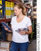 Woman standing near racks in build store holding notebook and samples. Стоковое фото, фотограф Яков Филимонов / Фотобанк Лори
