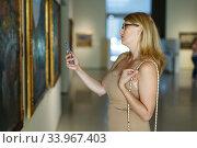 Купить «Woman taking photo in museum», фото № 33967403, снято 22 сентября 2018 г. (c) Яков Филимонов / Фотобанк Лори