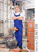 Купить «Construction worker mixing dry mortar with handheld mixer in bucket in overhauls indoors», фото № 33967599, снято 28 мая 2018 г. (c) Яков Филимонов / Фотобанк Лори
