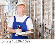 Купить «Focused construction worker inspecting room and planning upcoming repairs», фото № 33967627, снято 28 мая 2018 г. (c) Яков Филимонов / Фотобанк Лори