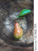 Купить «One juicy ripe pear with leaves lies on a wooden vintage dark background. Top view, copy space.», фото № 33968791, снято 20 августа 2018 г. (c) Tetiana Chugunova / Фотобанк Лори