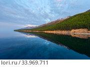 Lakeshore, reflected in water, Lake Baikal, Siberia, Russia. June 2016. Стоковое фото, фотограф Olga Kamenskaya / Nature Picture Library / Фотобанк Лори