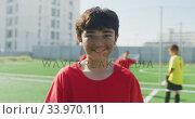 Купить «Caucasian soccer kid in red smiling and looking at camera», видеоролик № 33970111, снято 18 октября 2019 г. (c) Wavebreak Media / Фотобанк Лори