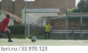 Купить «African American soccer kid in red scoring in a sunny day», видеоролик № 33970123, снято 18 октября 2019 г. (c) Wavebreak Media / Фотобанк Лори