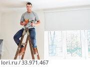 Купить «Junger Mann als Heimwerker mit Bohrmaschine sitzt auf einer Leiter bei der Haus Renovierung», фото № 33971467, снято 3 июля 2020 г. (c) age Fotostock / Фотобанк Лори