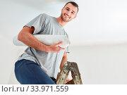 Купить «Junger Mann mit Tapete auf einer Leiter beim Tapezieren und Renovieren im neuen Eigenheim», фото № 33971559, снято 3 июля 2020 г. (c) age Fotostock / Фотобанк Лори