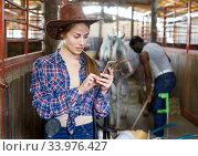 Woman farmer worker using phone in stable. Стоковое фото, фотограф Яков Филимонов / Фотобанк Лори