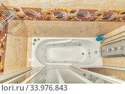 Small beige tile bathroom with bath tube. Редакционное фото, фотограф Ольга Сапегина / Фотобанк Лори