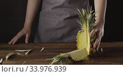 Купить «Panoramic view to falling quarter of fresh ripe pineapple on a wooden table. Girl's hands hold natural exotic fruit.», видеоролик № 33976939, снято 3 августа 2020 г. (c) Ярослав Данильченко / Фотобанк Лори