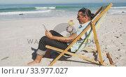 Senior Caucasian man sitting on sunbeds at the beach. Стоковое видео, агентство Wavebreak Media / Фотобанк Лори