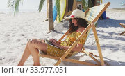 Купить «Caucasian woman sitting on a sunbed and using his laptop on the beach», видеоролик № 33977051, снято 25 февраля 2020 г. (c) Wavebreak Media / Фотобанк Лори