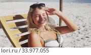 Caucasian woman sitting on a sunbed on the beach. Стоковое видео, агентство Wavebreak Media / Фотобанк Лори