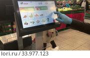 Покупатель в резиновых перчатках взвешивает лук в отделе свежих овощей и фруктов в супермаркете Окей. Редакционное видео, видеограф Кекяляйнен Андрей / Фотобанк Лори