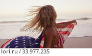 Купить «Caucasian woman holding and waving an US flag on the beach.», видеоролик № 33977235, снято 25 февраля 2020 г. (c) Wavebreak Media / Фотобанк Лори