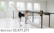 Caucasian female ballet dancer stretching up by the mirror in a bright studio. Стоковое видео, агентство Wavebreak Media / Фотобанк Лори