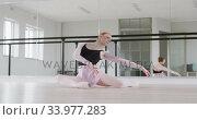 Купить «Caucasian female ballet dancer stretching up on the floor and preparing for dance class», видеоролик № 33977283, снято 24 октября 2019 г. (c) Wavebreak Media / Фотобанк Лори