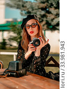 Купить «A young woman in a vintage black polka-dot dress with an old camera in her hands posing on the street», фото № 33981943, снято 7 июля 2020 г. (c) easy Fotostock / Фотобанк Лори