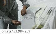 African American male car mechanic taking a protective cover off a car. Стоковое видео, агентство Wavebreak Media / Фотобанк Лори