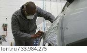 Купить «African American male car mechanic wearing a face mask and polishing a side of a car with a grinder», видеоролик № 33984275, снято 6 ноября 2019 г. (c) Wavebreak Media / Фотобанк Лори