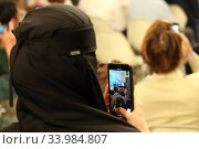 Купить «Riyadh, Saudi Arabia, woman in niqab filming an event with her mobile», фото № 33984807, снято 26 февраля 2020 г. (c) Caro Photoagency / Фотобанк Лори