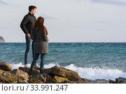 Купить «Двое молодых людей стоя на каменном берегу моря обсуждают сложившуюся ситуацию», фото № 33991247, снято 22 марта 2020 г. (c) Иванов Алексей / Фотобанк Лори