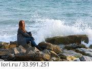 Девушка в осеннюю ветреную погоду сидит у моря на каменистом берегу. Стоковое фото, фотограф Иванов Алексей / Фотобанк Лори
