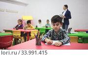 Portrait of little diligent schoolboy writing at lesson in elementary school. Стоковое видео, видеограф Яков Филимонов / Фотобанк Лори
