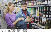 Happy married couple chooses champagne in the store. Стоковое видео, видеограф Яков Филимонов / Фотобанк Лори