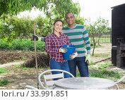 Cheerful latin american couple of gardeners on spring day. Стоковое фото, фотограф Яков Филимонов / Фотобанк Лори