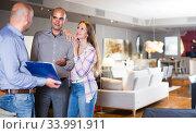 Seller is showing prices in home furnishings store. Стоковое фото, фотограф Яков Филимонов / Фотобанк Лори