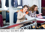 Women choosing warm coats in boutique. Стоковое фото, фотограф Яков Филимонов / Фотобанк Лори