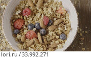 Купить «Top view of preparing healthy breakfast from falling granola, fr», видеоролик № 33992271, снято 7 июля 2020 г. (c) Ярослав Данильченко / Фотобанк Лори