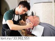 Portrait of young man barber shaving man's head. Стоковое фото, фотограф Яков Филимонов / Фотобанк Лори