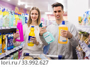 Fine couple choosing household detergents. Стоковое фото, фотограф Яков Филимонов / Фотобанк Лори