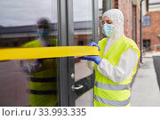 Купить «healthcare worker sealing door with caution tape», фото № 33993335, снято 24 апреля 2020 г. (c) Syda Productions / Фотобанк Лори