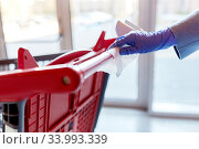 Купить «hand cleaning shopping cart handle with wet wipe», фото № 33993339, снято 30 апреля 2020 г. (c) Syda Productions / Фотобанк Лори