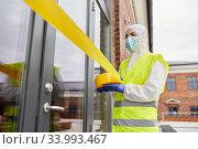Купить «healthcare worker sealing door with caution tape», фото № 33993467, снято 24 апреля 2020 г. (c) Syda Productions / Фотобанк Лори